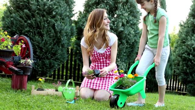 HD: Famille heureuse ensemble dans un jardin arrière-cour. - Vidéo