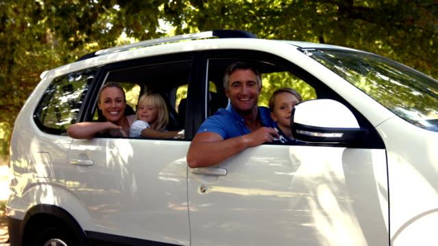 vídeos de stock e filmes b-roll de feliz família preparar-se para a viagem por estrada e olhando para a câmara - homem casual standing sorrir