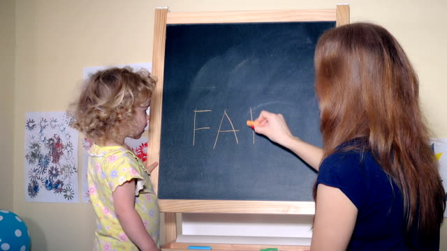 Happy family girls mom and daughter writing word father on black chalk board Happy family girls mom and daughter writing word father on black chalk board. Static closeup shot. 4K alphabet stock videos & royalty-free footage