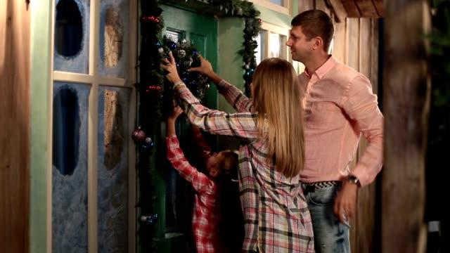 Happy family hanging Christmas wreath on the door video