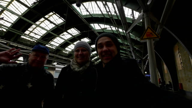 Happy family having fun and sending greetings on train station in Berlin in slow motion in 4k slow motion 60fps