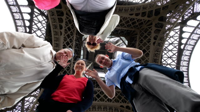 Happy family having fun and sending greetings under the Eiffel Tower in Paris in 4k slow motion 60fps