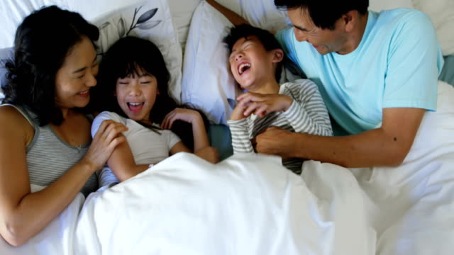 Happy family having fun on bed in the bed room 4k video