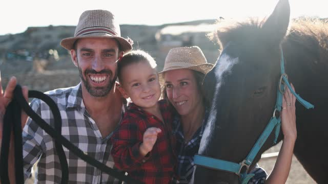 Happy family having fun together with their horse at ranch farm
