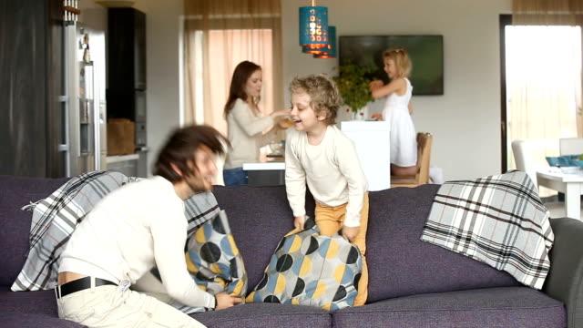 lycklig familj ha kul med barnen i mysigt vardagsrum - cosy pillows mother child bildbanksvideor och videomaterial från bakom kulisserna