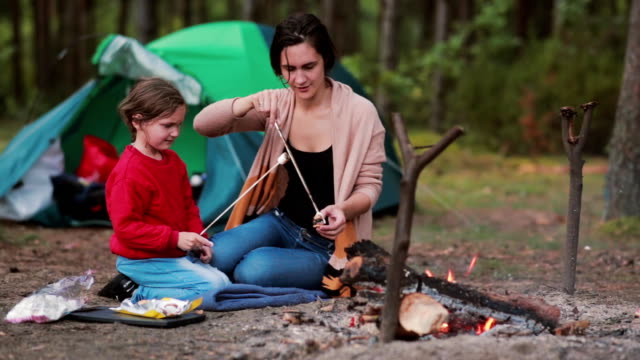 Happy family having great time together in the nature. Mom teaches her daughter to cook marshmallows on open fire video