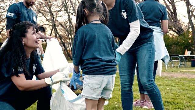 Happy family help neighbors clean up their community