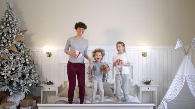 lycklig familj håller julklappar och hoppar på sängen - christmas gift family bildbanksvideor och videomaterial från bakom kulisserna