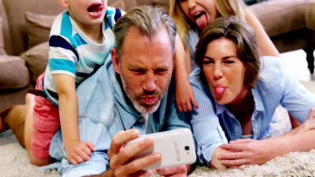 Happy Family im liegen auf Teppich und sprechen ein Selbstporträt auf Handy – Video
