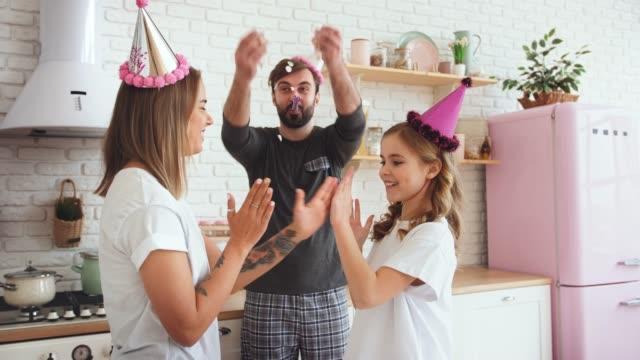 lycklig familj i pyjamas med en dotter dansar och firar födelsedag i köket under online födelsedagsfest. pappa kastar konfetti, slow motion - birthday celebration looking at phone children bildbanksvideor och videomaterial från bakom kulisserna