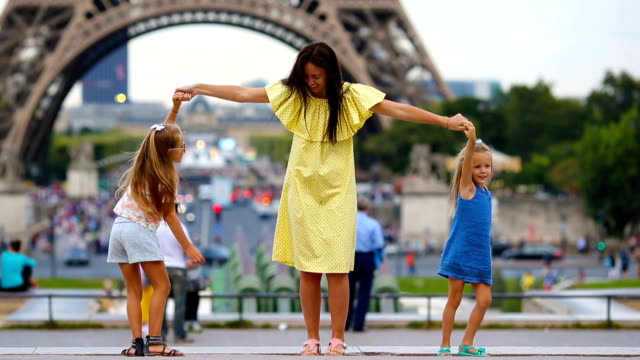 Happy family in Paris near Eiffel tower. French summer holidays, travel and people concept - vídeo
