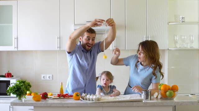 lycklig familj är matlagning i köket. pappa bryter ägg långsam rörelse - enbarnsfamilj bildbanksvideor och videomaterial från bakom kulisserna