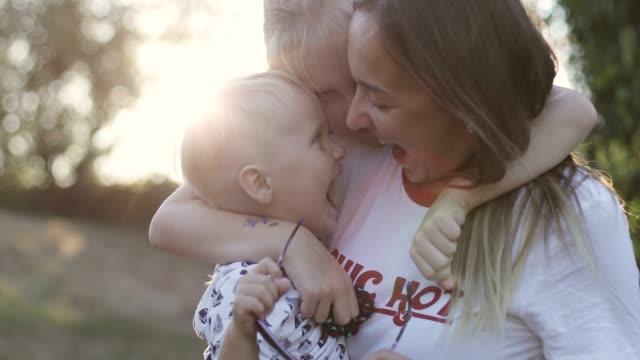 幸せな家族を公園で夕日の背景に抱いています。 - 兄弟姉妹点の映像素材/bロール