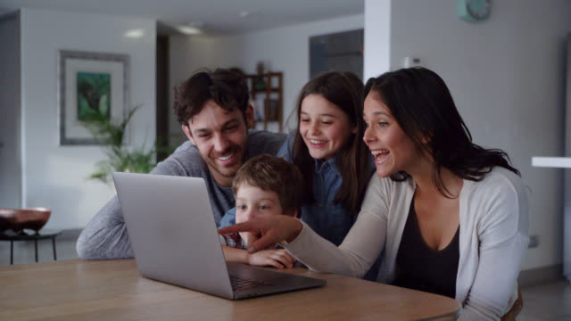 happy family looking at videos on laptop while kids point at screen and talk smiling - family home video stock e b–roll