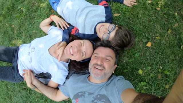 happy family lying on grass - leżeć filmów i materiałów b-roll