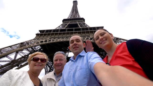 glückliche familie machen selfie unter dem eiffelturm in paris in zeitlupe in 4k - blickwinkel aufnahme stock-videos und b-roll-filmmaterial