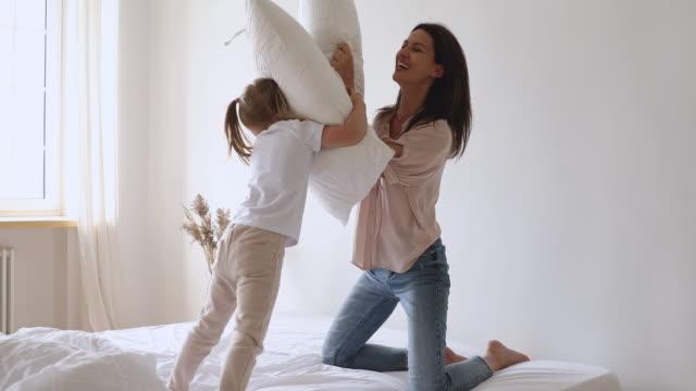 lycklig familj mamma och dotter njuta av kudde slåss på sängen - cosy pillows mother child bildbanksvideor och videomaterial från bakom kulisserna