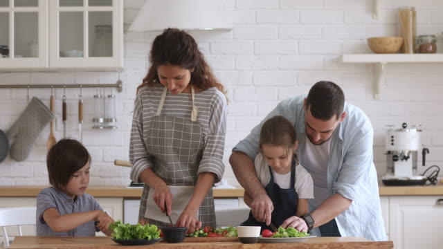 Happy family mom dad and kids siblings cooking together