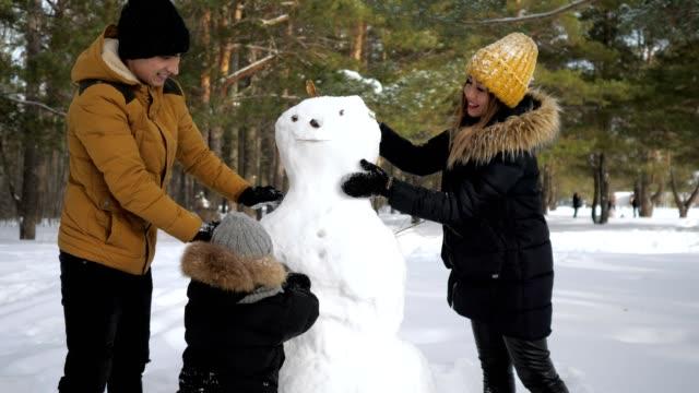 vídeos y material grabado en eventos de stock de feliz familia mamá, papá e hijo están haciendo un hombre de nieve en el parque de la ciudad de invierno. - snowman