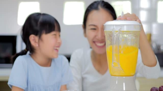 幸せな家族のお母さんを教えるかわいい女の子を準備し、健康 smoothei を初めて調理します。タイのファミリー - 母娘 笑顔 日本人点の映像素材/bロール