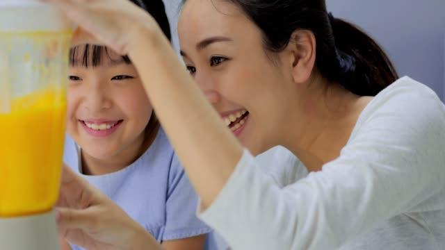 vidéos et rushes de maman heureuse de famille enseignant la fille mignonne préparant et cuisinant la bonne santé de lisser pour la première fois. familles en thaïlande - cuisine non professionnelle