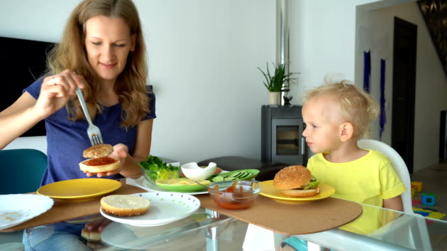 happy family mother and child making burgers and eating. gimbal motion - вредное питание стоковые видео и кадры b-roll