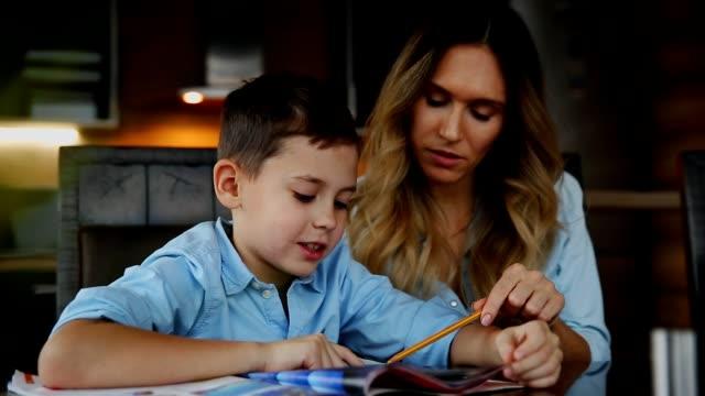 2 人の子供の幸せな家族母親助ける台所の大きなテーブルに座っている彼らの宿題をする息子 ビデオ