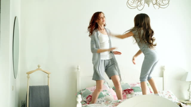 Happy family of cute daughter and young mother jumping and dancing on bed while have fun during morning on holidays at home