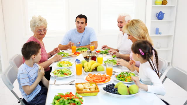 Happy family of eating together at the table. video