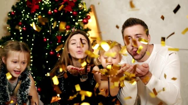 lycklig familj av fyra blåser guldglitter konfetti hemma i slow motion under julfest. dekorerad julgran på bakgrunden. slowmotion skott - christmas gift family bildbanksvideor och videomaterial från bakom kulisserna