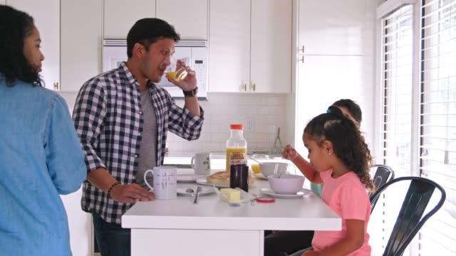 glückliche familie von vier, die in der küche frühstücken - frühstück stock-videos und b-roll-filmmaterial