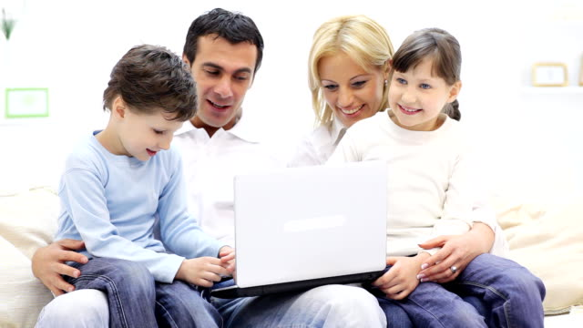 Happy family of four people sitting with laptop computer. video