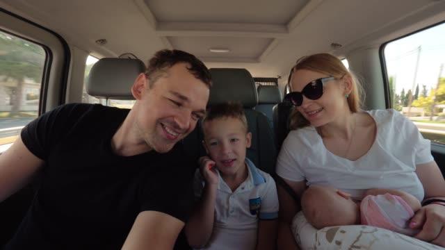 vídeos de stock, filmes e b-roll de família feliz de quatro que viaja pelo carro - veículo terrestre