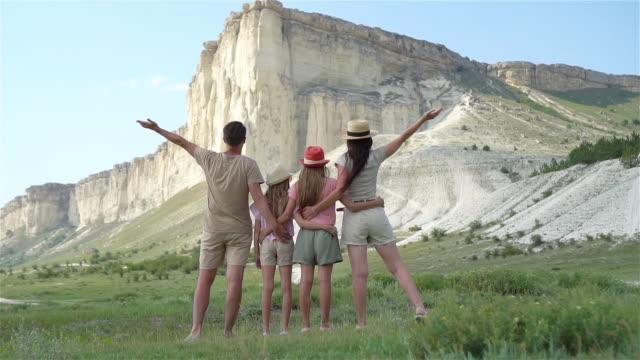 happy family of four walking in the mountains - wschodnio europejski filmów i materiałów b-roll