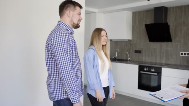 Happy family of husband and wife buying new modern apartment