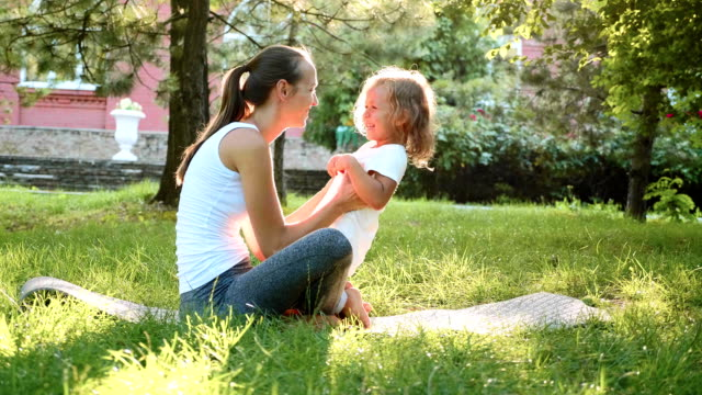 happy family of young sporty mother and little cute daughter having fun outdoors - fare il solletico video stock e b–roll