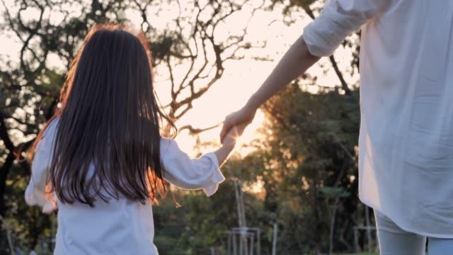 vídeos de stock, filmes e b-roll de a família feliz em passeios da natureza no verão. a mulher está gastando o tempo com sua filha charming pequena ao ar livre durante o por do sol. parenting relaxado - mão humana