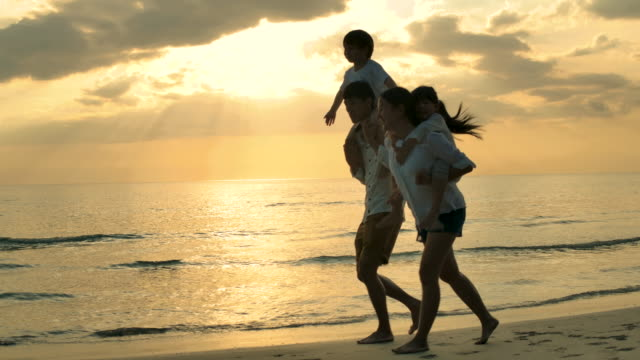 Happy Family on the Beach at Sunset.