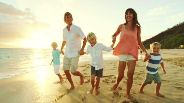 Familia feliz en la playa al atardecer - vídeo
