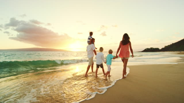 happy family on the beach at sunset - vacanze video stock e b–roll