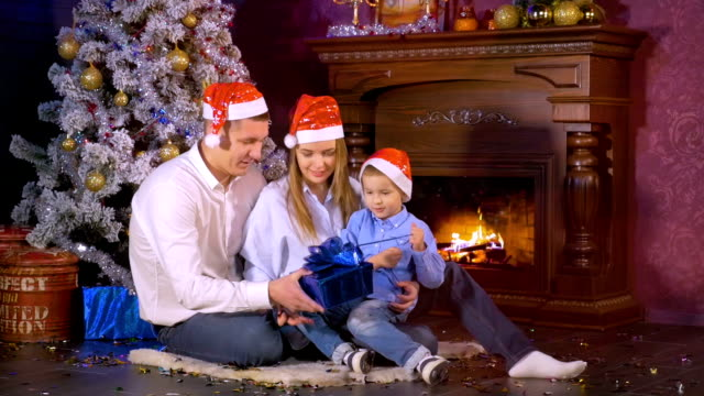 Happy family open Christmas gifts near christmas New Year fireplace. video