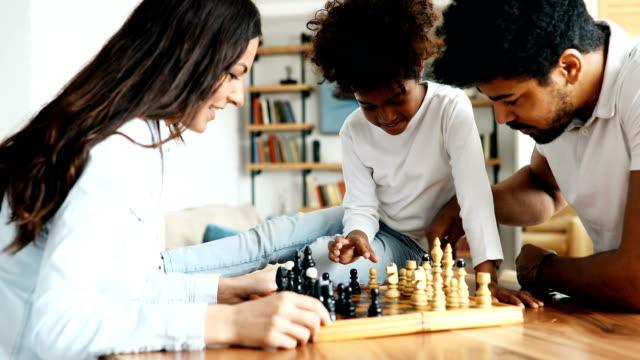 glückliche familie zusammen schach zu spielen, die zu hause - bauholz brett stock-videos und b-roll-filmmaterial