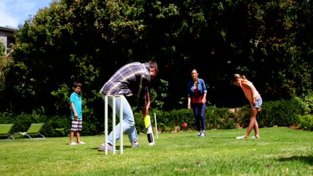 Happy family playing cricket video