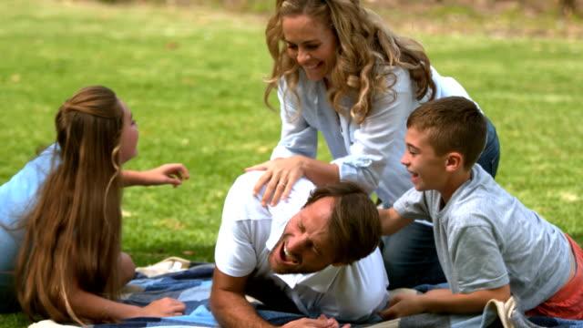 famiglia felice giocando insieme in un parco - fare il solletico video stock e b–roll