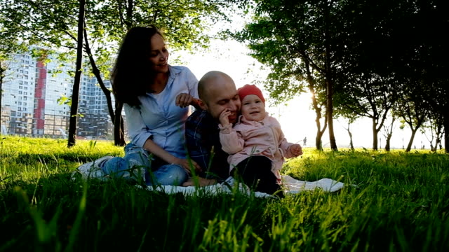 Happy family playing with little child in summer park at sunset. A little baby girl tweaks her father's nose and laughs Happy family playing with little child in summer park at sunset. A little baby girl tweaks her father's nose and laughs. pinching stock videos & royalty-free footage