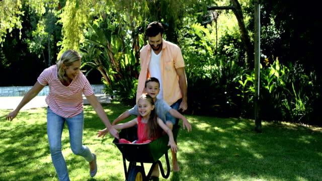 lycklig familj spelar med skottkärran i trädgården - skyffel bildbanksvideor och videomaterial från bakom kulisserna