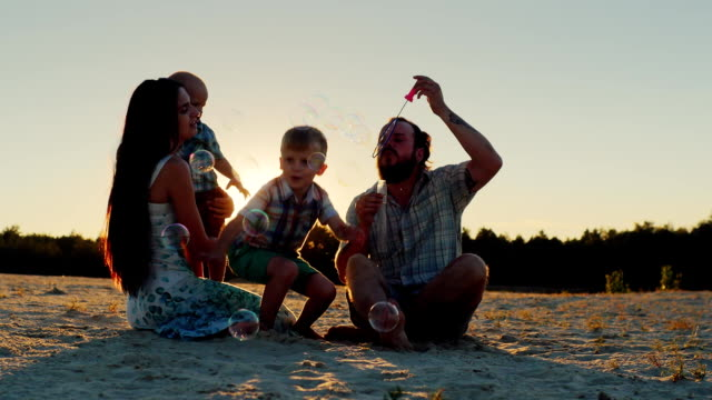 Happy family playing with two kids - blow bubbles video