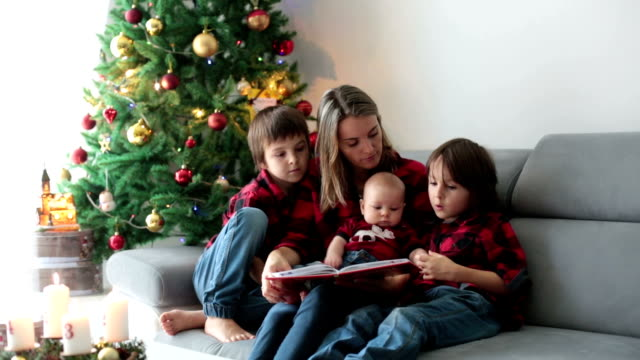Happy family portrait on Christmas, mother, reading a book to her three children sitting on couch at home, chritmas decoration around them video