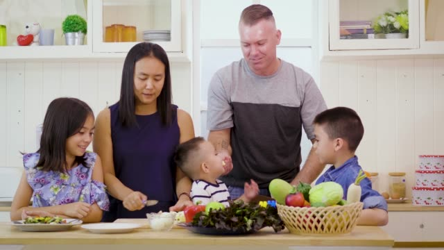 Happy family preparing vegetables mix salad in kitchen at home together