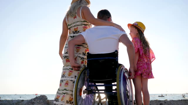 happy family raising hands looking at waves, rear view, husband in wheelchair hug wife and little girl, disabled hugs happy family raising hands looking at waves husband in wheelchair hug wife and little girl wheelchair stock videos & royalty-free footage